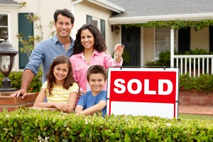 family-in-front-of-sold-sign